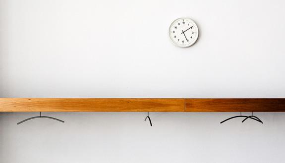 Garderobe mit Uhr, leere Kleiderbügel hängen dort