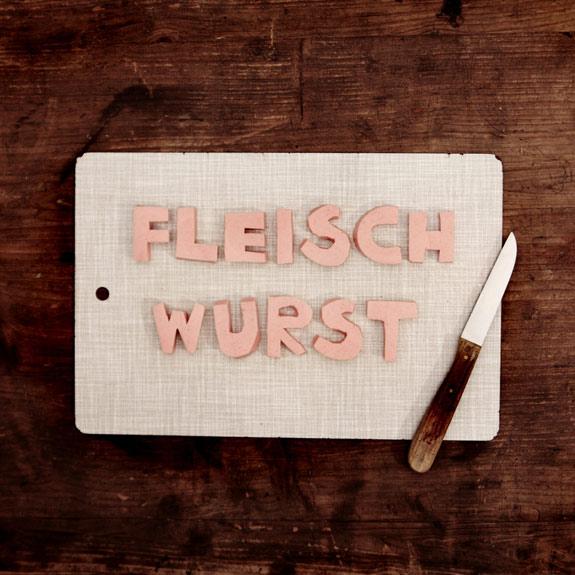Auf einem Schneidebrett: mit Wurst steht geschrieben: Fleischwurst; ein Messer liegt auf dem Brett