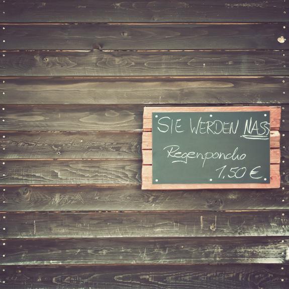 An einer Holzwand hängt eine Tafel. Darauf steht: Sie werden nass, Regenponcho 1,50 Euro