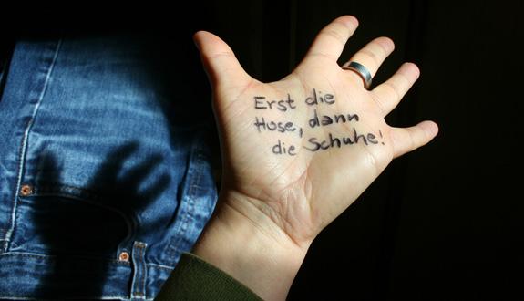 Auf einer Hand steht geschrieben: Erst die Hose, dann die Schuhe